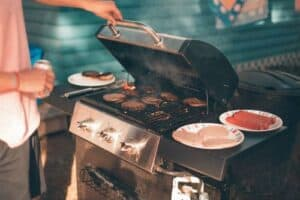 person cooking on gas grill