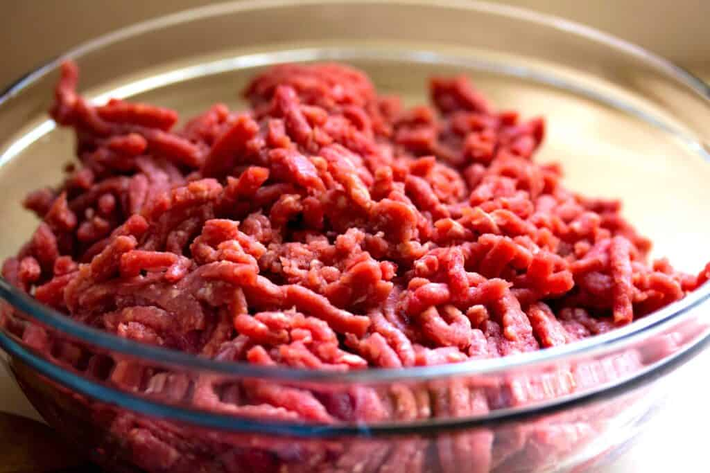 bowl of ground meat while comparing best electric and best manual meat grinders